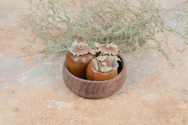 Плоды мушмулы в миске с травой на оранжевой поверхности.
