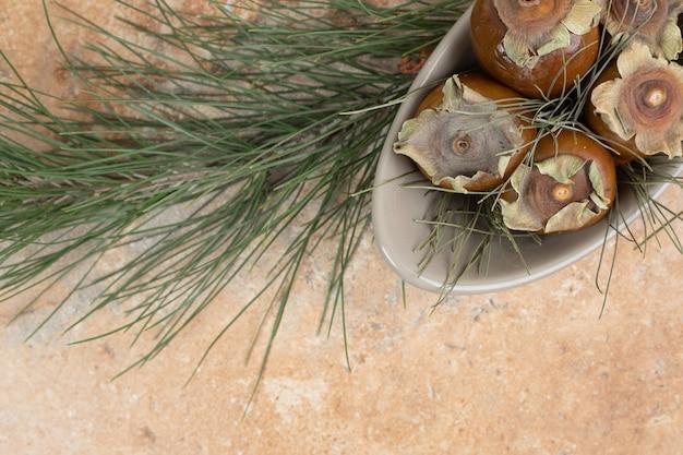 Плоды мушмулы в миске с травой на оранжевом столе.