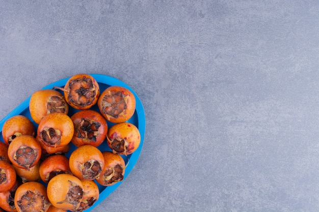 Medlars isolated in a wooden platter on the ground