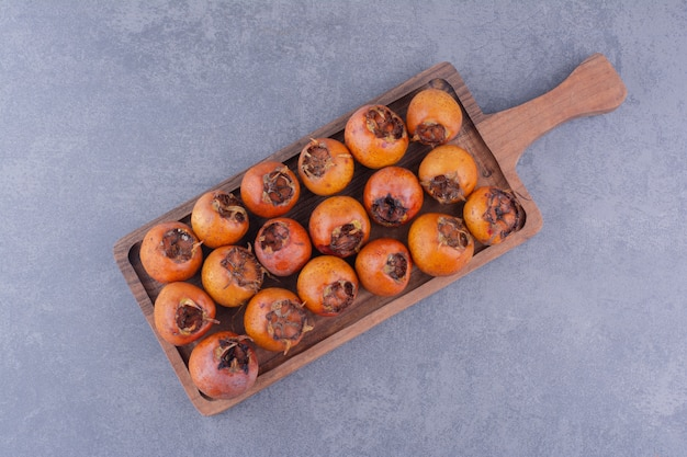 Медлары на деревянном блюде на сером фоне.