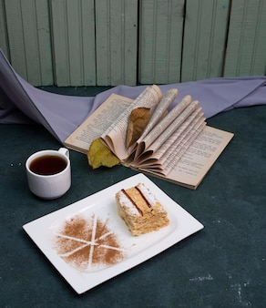 Medovik cake with cocoa powder and a cup of tea on the stone table.
