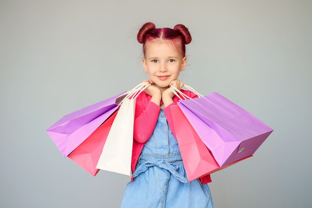 Meet the discounts. happy little baby girl smiles with paper shopping bags.
