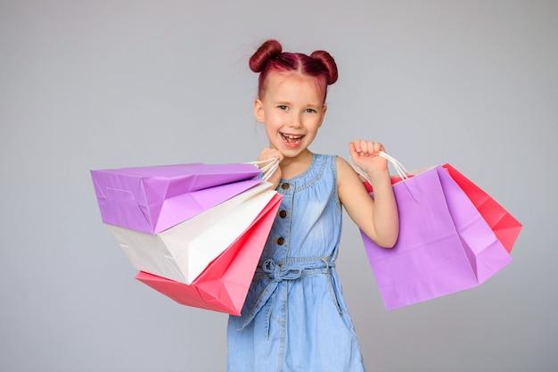 할인을 만나보세요. 종이 쇼핑백 함께 행복 한 작은 아기 소녀 미소.