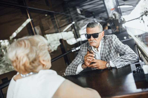 モダンなレストランで2人の先輩に会い、タバコを吸っている男性。