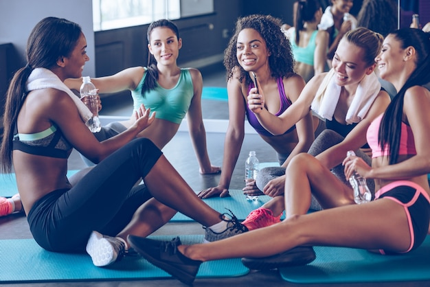 マットの上で会いましょう。ジムでエクササイズマットに座って笑顔でスマートフォンを使用して何かを話し合うスポーツウェアの美しい若い女性