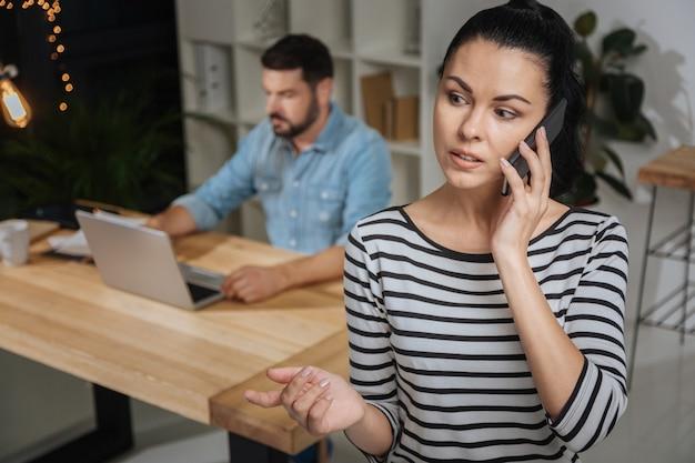 Организация встреч. приятная красивая милая женщина держит мобильный телефон и договаривается о встрече, работая на своего босса