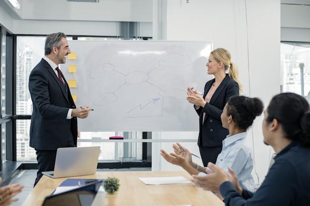 Встреча бизнес-концепции. кавказская женщина с начальником предлагает информацию на борту людям в команде для планирования работы группы в конференц-зале. люди на встрече были заинтересованы в объяснении.