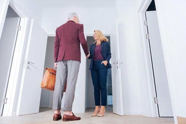 Meeting client. blonde-haired appealing pleasant estate agent meeting her client at the doorstep of luxury apartment