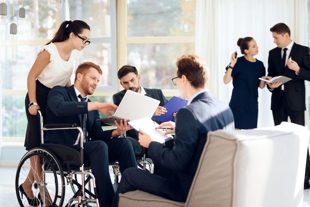 Meeting of disabled people in bright room with wide windows.
