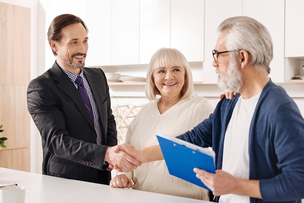 집의 미래 소유자를 만나십시오. 악수하고 계약서를 제시하면서 노부부 고객과 만나는 경험 많은 긍정적 인 부동산 중개인을 기쁘게 생각합니다.