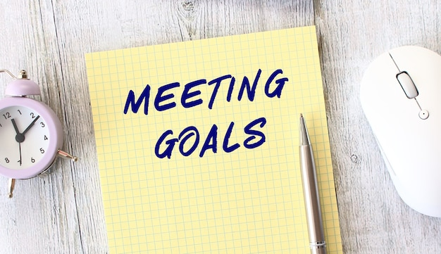 Meeting goals text written in a notebook lying on a wooden work table. business concept.