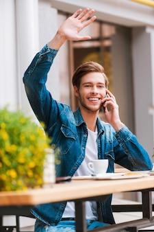 カフェで友達に会う。携帯電話で話し、手を振って笑顔の若い男