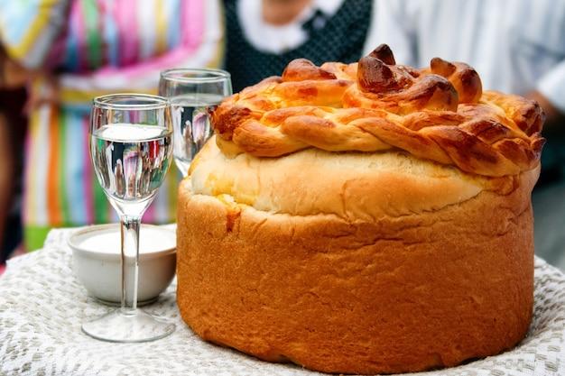 Встреча молодоженов после свадьбы по славянским свадебным традициям: буханка хлеба, соль и водка.
