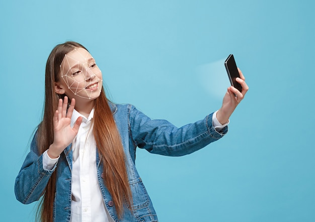 Встреча знаний. девушка со смартфоном в джинсовом костюме, стоя на синем фоне. технология распознавания лиц по полигональной сетке. концепция кибербезопасности, бизнеса, работы, образования.