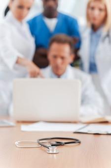 医療専門家の会議。聴診器が前景に置かれている間、何かについて話し合い、ラップトップを見ている自信のある医師のグループ