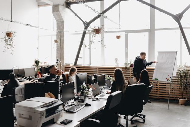 Встреча коллег. команда сидит за столами с компьютерами и ноутбуками и слушает коллегу, стоящего у флипчарта в просторном светлом современном офисе.