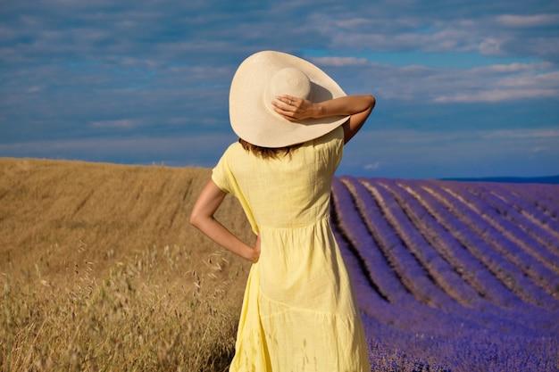 2つの世界の出会い:小麦とラベンダー畑の間にある黄色いドレスを着た女の子