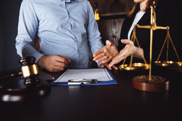 Meeting in an office, lawyers or attorneys discussing a document or contract agreement.