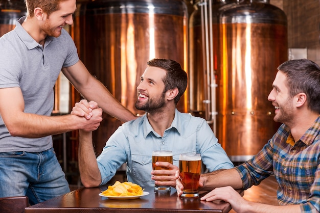 Meeting old friend. three happy young men sitting in beer pub together while two of them handshaking