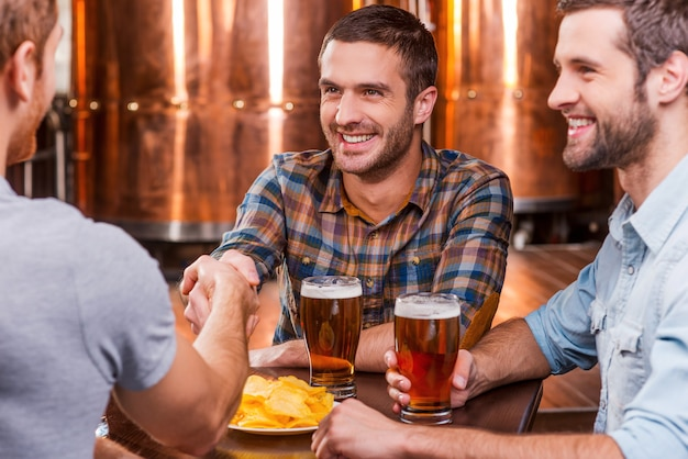 Meeting old friends. three happy young men sitting in beer pub together while two of them handshaking