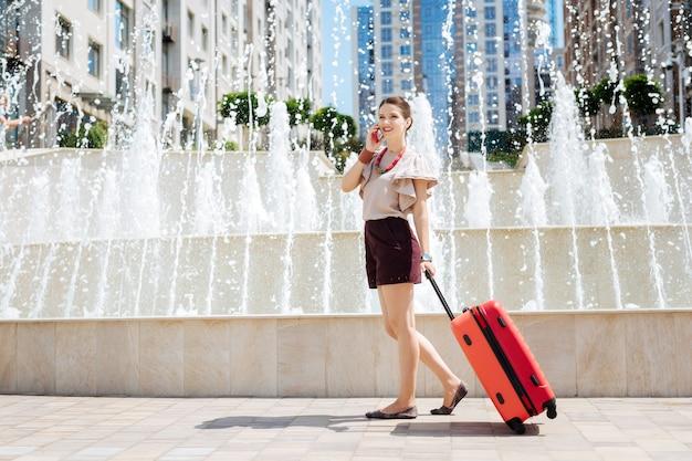 ミーティングポイント。噴水の近くに立っている間電話で話している快適な素敵な女性