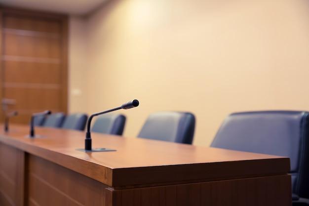 Конференц-зал или зал заседаний с профессиональным микрофоном на столе.