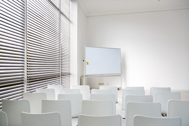大きな白い教育委員会と白い椅子のある会議室。モダンなライトオフィスの素敵な広々とした部屋。