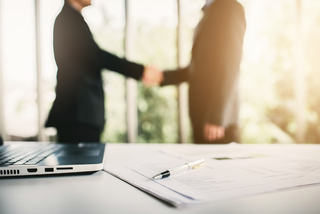 Meeting room with document with businessman shaking hands in background