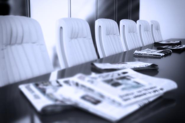 テーブルの上に新聞がある会議室