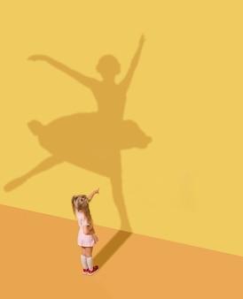 미래를 만나다. 어린 시절과 꿈의 개념. 아이와 노란색 스튜디오 벽에 그림자 개념적 이미지. 어린 소녀는 발레리나, 발레 댄서, 예술가가되고 경력을 쌓기를 원합니다.
