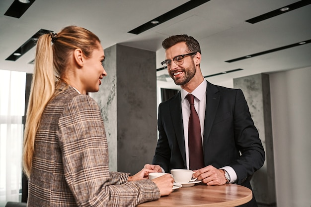 Meeting of two friends. businessman and woman at hotel hall drinking coffee. man is holding woman's hand