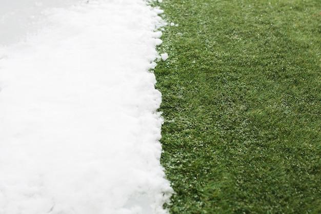 冬と春のコンセプトの背景の間で、白い雪と緑の草に出会うクローズアップ。春の概念イメージ。