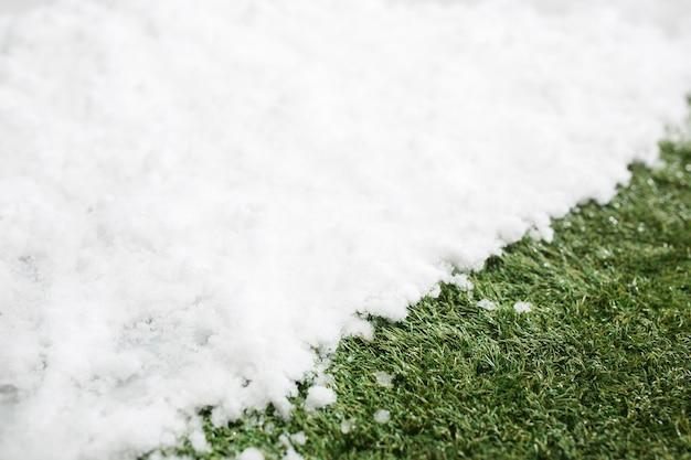 白い雪と緑の草に出会うクローズアップ。冬と春のコンセプトの背景の間。