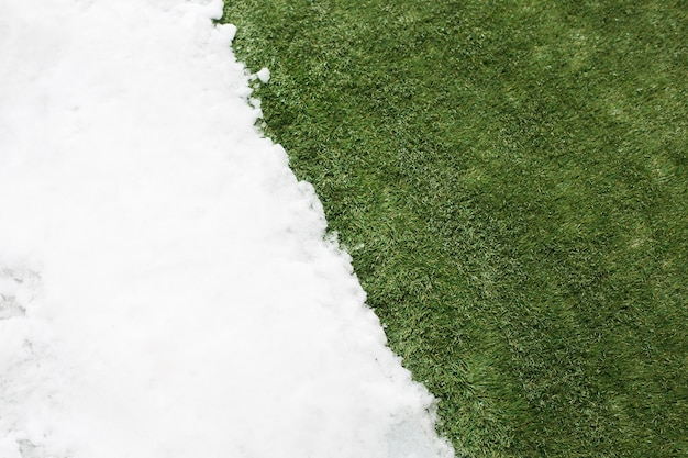 Meeting white snow and green grass close up. between winter and spring concept background.