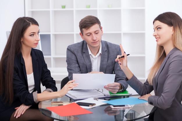 オフィスでのエージェントとのミーティング、賃貸アパートまたは家の購入、取引を締結する準備ができている不動産のバイヤー、不動産購入のための文書に署名した後の不動産業者と握手する家族カップル