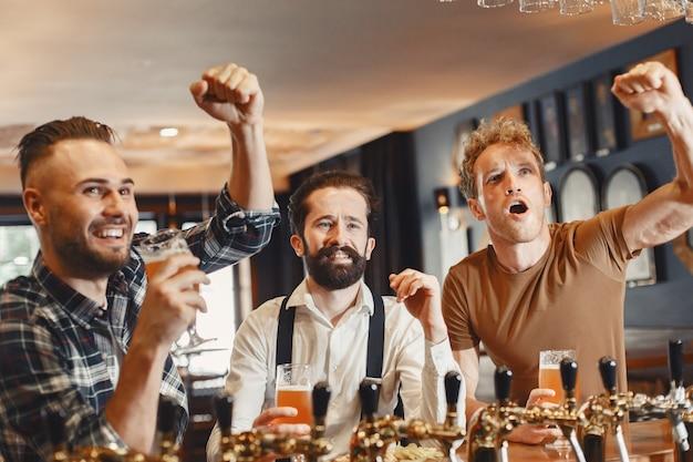 Incontro con i migliori amici. tre giovani uomini felici in abbigliamento casual a parlare e bere birra seduti insieme al bar.
