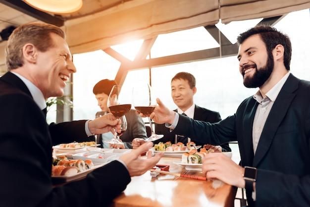Встреча с китайскими бизнесменами в костюмах в ресторане.