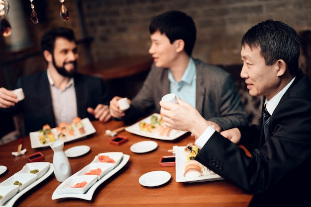 Meeting with japanese businessmen in suits in restaurant.
