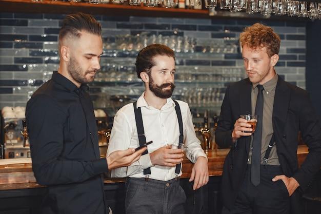 親友との出会い。カジュアルな服装で3人の幸せな若い男性が一緒にバーに座って話したり、ビールを飲んだりします。彼の手で電話を持っている男。