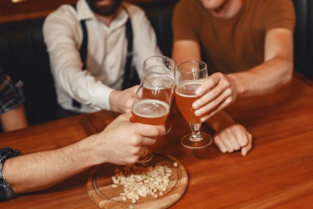 가장 친한 친구와의 만남. 함께 바에 앉아있는 동안 얘기하고 맥주를 마시는 캐주얼 착용 세 행복 젊은 남자.
