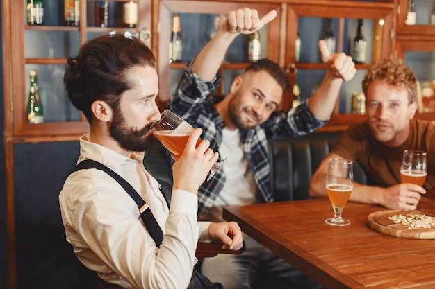 Встреча с лучшими друзьями. трое счастливых молодых людей в повседневной одежде разговаривают и пьют пиво, сидя в баре вместе.