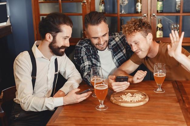 親友との出会い。カジュアルな服装で3人の幸せな若い男性が一緒にバーに座って話したり、ビールを飲んだりします。