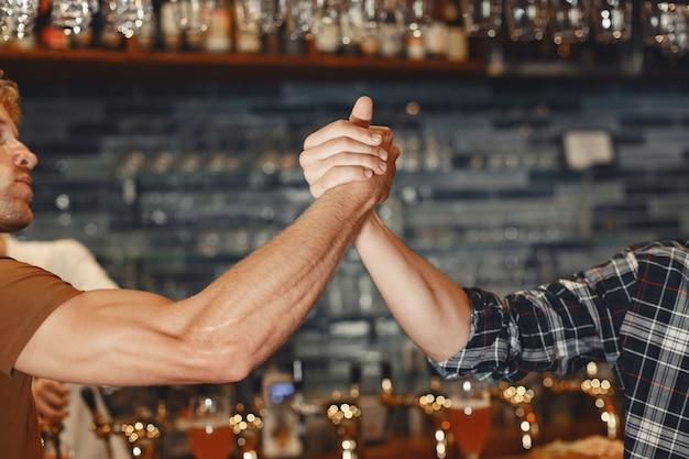 親友との出会い。カジュアルな服装の2人の幸せな若い男性は、一緒にバーに座って話したりビールを飲んだりします。