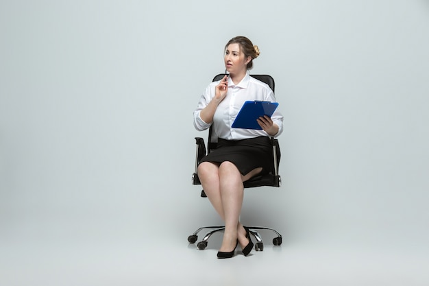 Meeting. young woman in office attire. body positive female character, feminism, loving herself, beauty concept. plus size businesswoman on gray wall. boss, beautiful. inclusion, diversity.