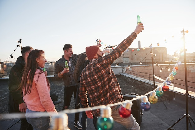 Meets dawn. holidays on the rooftop. cheerful group of friends raised their hands up with alcohol