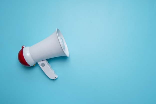 Megaphone announcement on blue wall with copy space