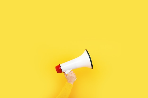 Megaphone in hand on a yellow background