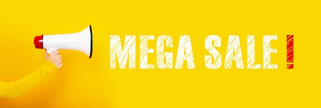 Megaphone in hand on a yellow wall, concept mega sale,
