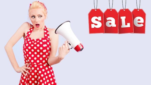 Мегафон, женщины, крики. pin up девушка в красном платье кричит в мегафон с бирками распродажи