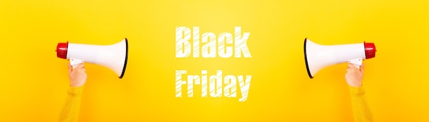 Megaphones in hands and inscription black friday on a yellow background, panoramic image, concept sales